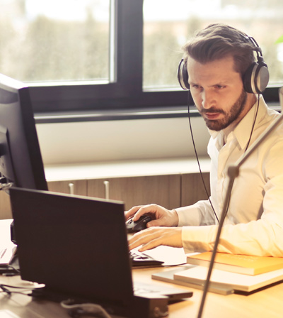 Man with headset glaring at computer