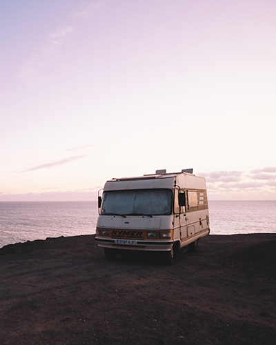 Camper parked on the beach in front of a lake
